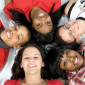 Five smiling people lay with their heads together in a circle.